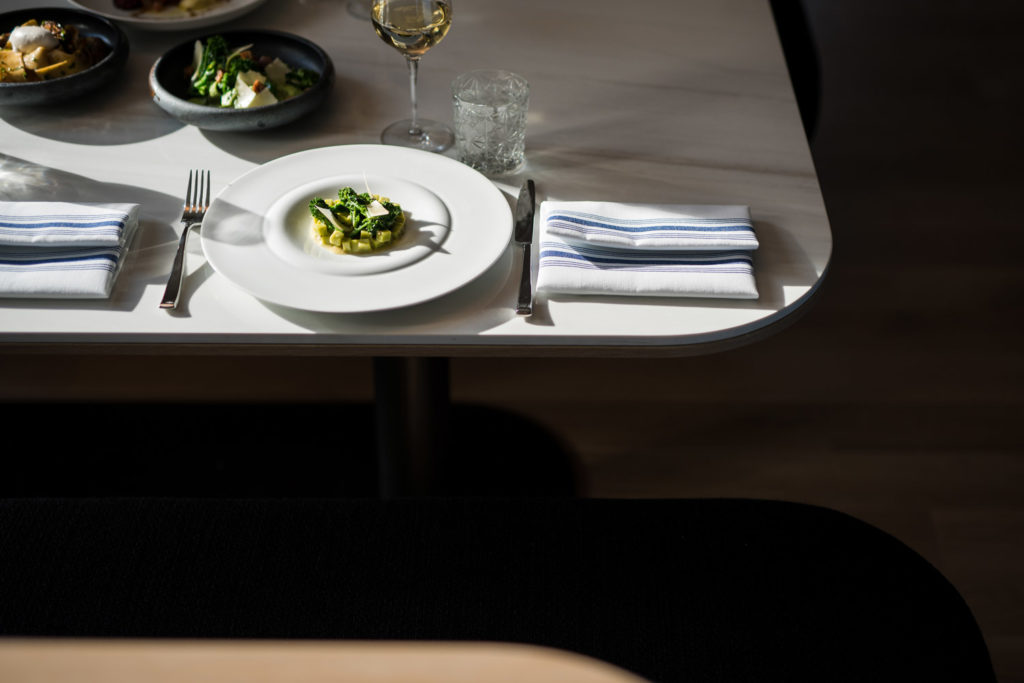dining table with plated food and wine glasses with artistic shadows
