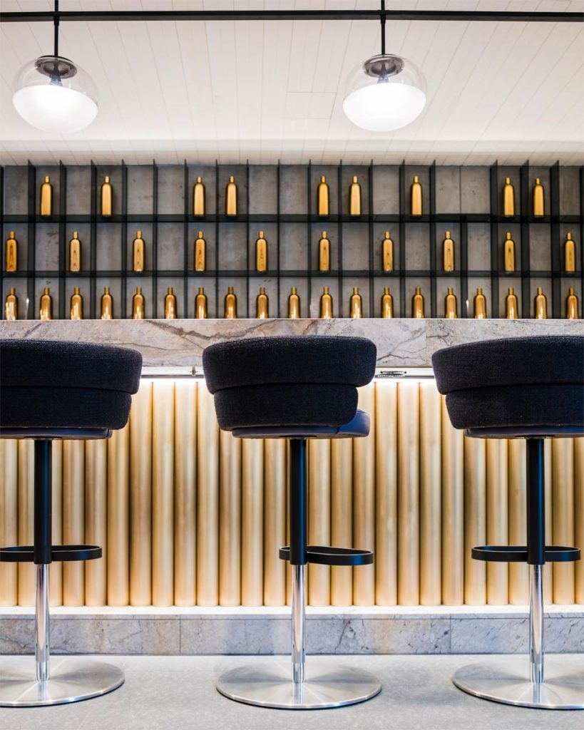 three black padded bar stools in front of elegant gold bar