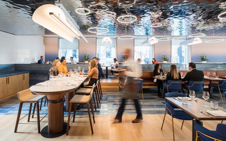 server walking through bustling restaurant interior