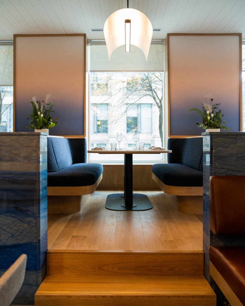 blue dining booth in front of large window