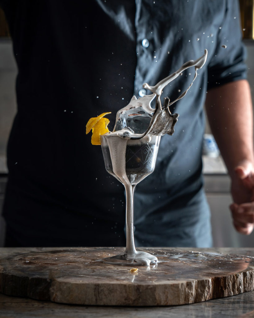 bartender dropping garnish into cocktail with large splash