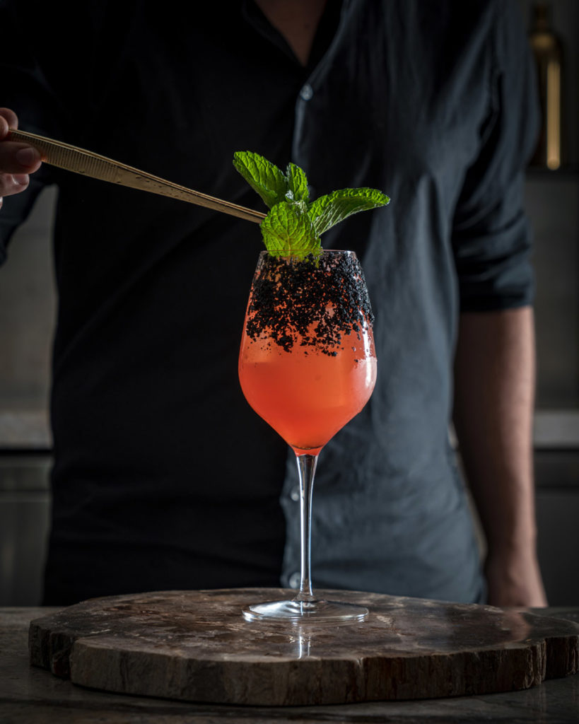 bartender delicately placing garnish into long stemmed cocktail