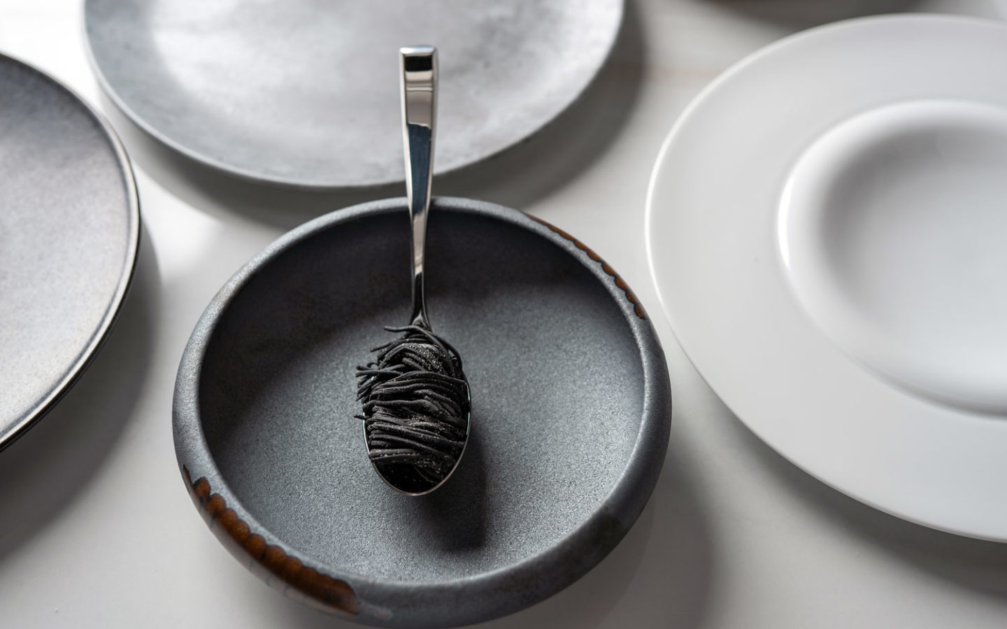 black pasta noodles wrapped around stainless steel spoon